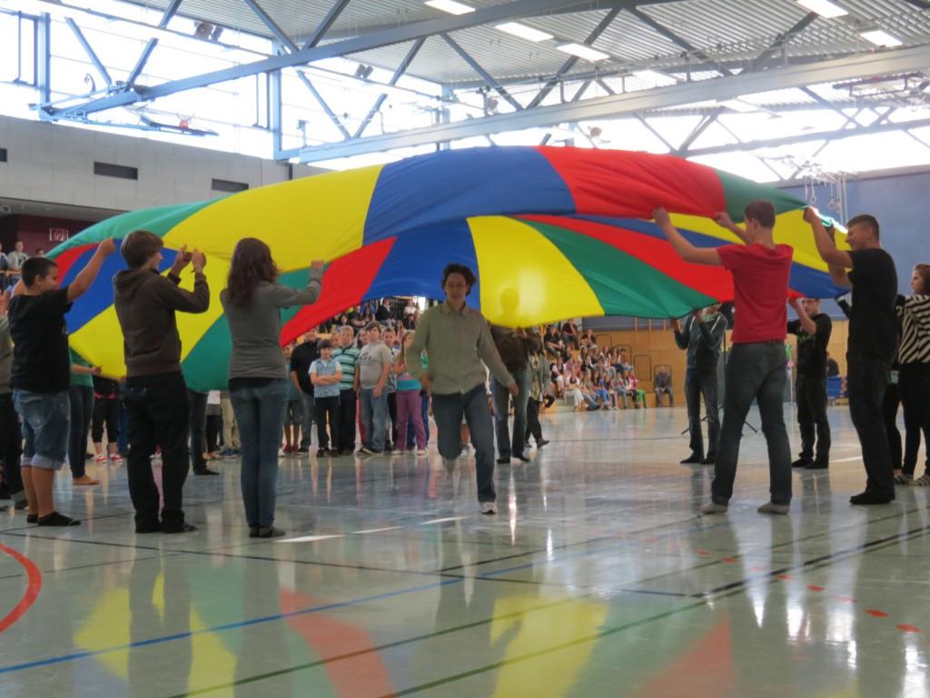 """Die Schulgemeinschaft der Paul-Schneider-Schule nimmt ihre neuen Fünftklässler unter ihren Schutz und Schirm. Mit einem sportlichen Aufnahmeritual feiert das Sohrener Bildungsinstitut ihre neuen """"Fünfer""""."""