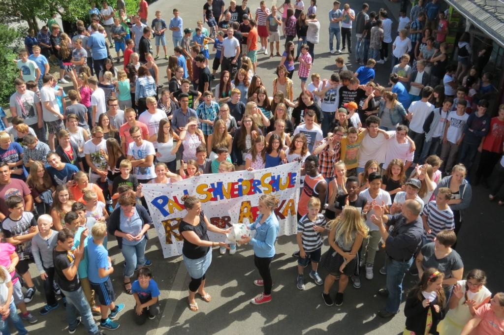 """Symbolisch mittels eines """"Sparschweins"""" überreicht Celina Kostecki (vorne, rechts) die Spenden des """"Run for Africa""""-Spendenlaufs an Stefanie Linden (vorne, links). Die Schulgemeinschaft der Paul-Schneider-Schule applaudiert stolz: über 4660 Euro kamen zusammen."""